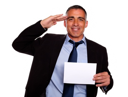 Portrait of a friendly senior businessman giving a military salute, smiling and holding a white card with copyspace against white background photo