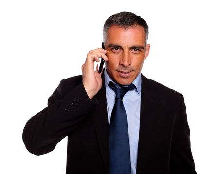 Portrait of a hispanic professional businessman conversing with a mobile looking to you against white background photo