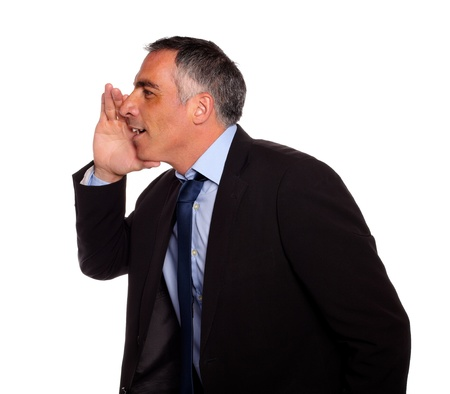 Portrait of a hispanic senior businessman on black suit whispering against white background photo