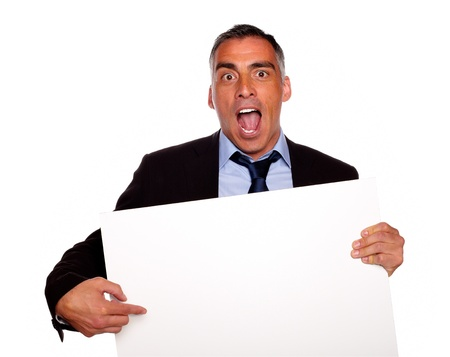 Portrait of a broker screaming, pointing and holding a white card with copyspace on isolated background