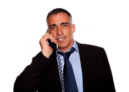 Portrait of a latin charismatic businessman smiling with a phone on black suit against white background photo