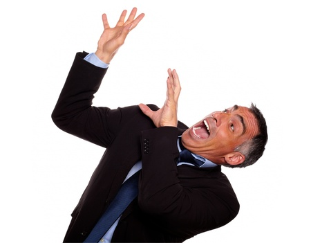 Portrait of a excited hispanic businessman screaming with hands up while falling down against white background photo