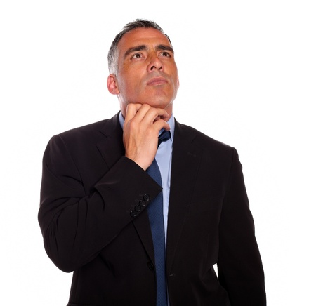 Portrait of a meditative businessman touching the chin while thinking on isolated background photo