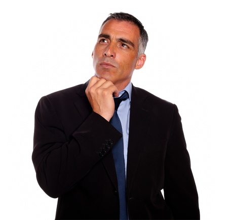 Portrait of a peaceful and reflective man touching the chin while thinking on black suit on isolated background photo