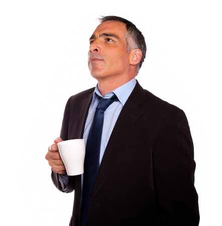 Portrait of a reflective business man with a white mug on isolated background photo