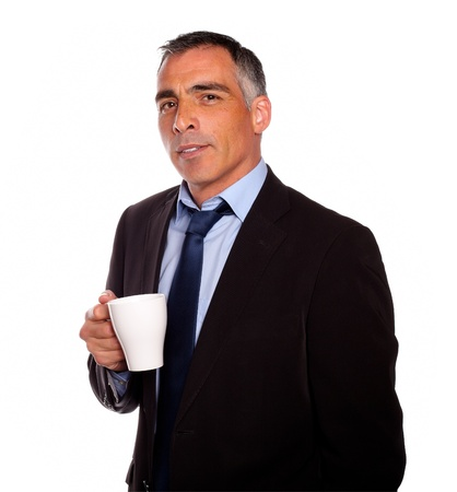 Portrait of a reflective charming man with a white mug on black suit on isolated background photo
