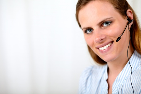 Close up portrait of a friendly blonde secretary smiling and talking on earphone photo