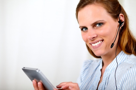 Close up portrait of a pretty woman smiling on earphone and holding a tablet PC photo