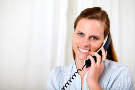 Close up portrait of a lovely beautiful blonde young woman smiling and speaking on phone at workplace photo