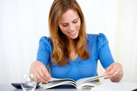 Portrait of a beautiful blonde female studying on blue blouse at home