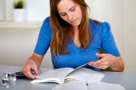 Portrait of a adult pretty woman reading a book at home indoor photo