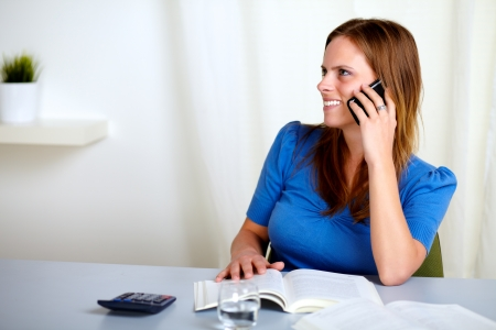 Portrait of a charming blonde lady talking on mobile phone at home indoor Stock Photo - 14159293