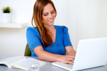 Portrait of a attractive blonde woman learning on laptop at home indoor photo