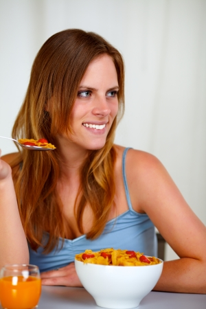 Portrait of a caucasian young woman smiling and eating healthy meal at home indoor photo