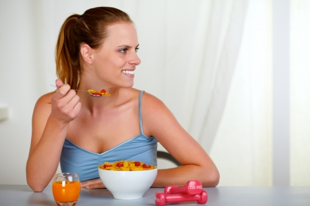 eating right: Portrait of a beautiful young woman looking to the right and eating healthy meal at home indoor