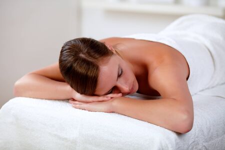 Portrait of a young woman lying on a stretcher at spa indoor Stock Photo