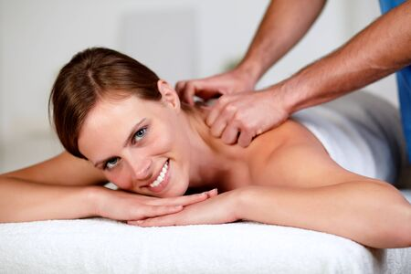 Closeup portrait of a young woman receiving a relaxed massage at a spa looking at you photo