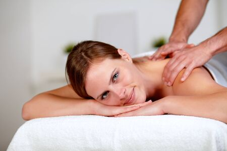 Portrait of a young blonde woman relaxing at a spa while receiving a massage at spa resort photo