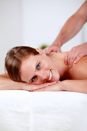 Close-up portrait of a young blonde girl relaxing at a spa while receiving a massage at spa resort with copyspace photo