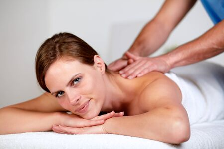 Close-up portrait of a pretty young blonde woman relaxing at a spa while receiving a massage at spa resort looking at you photo