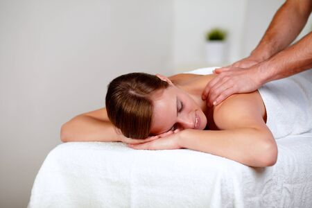 Portrait of a young woman with eyes closed receiving a massage at a spa day photo