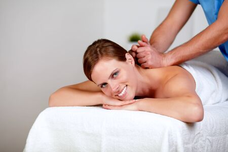 Portrait of a young female getting a back massage by a masseuse at spa resort photo
