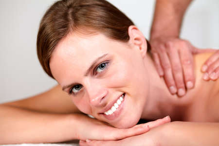 Close-up portrait of a lovely pretty woman smiling and relaxing while getting a massage from a professional masseuse at spa Stock Photo - 14248043