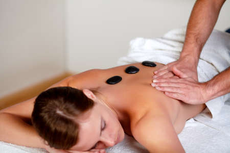 Close-up portrait of a young girl relaxing at a day spa, hot stone massage treatment photo
