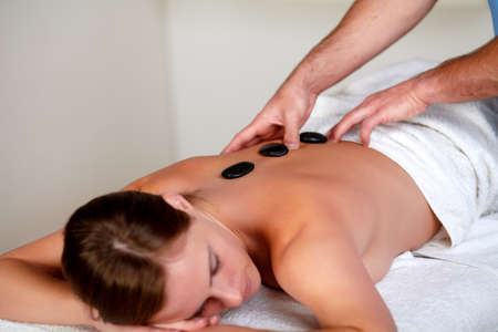 Close up of a beautiful woman getting a massage with hot stones at a spa resort photo