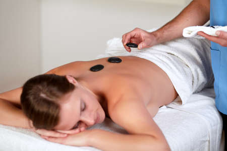 Close up of a woman relaxing while having a hot stone massage at a health spa resort photo
