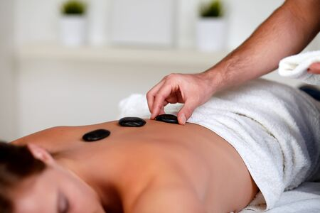Close up portrait of a tired woman relaxing at a spa and receiving a hot stone massage photo