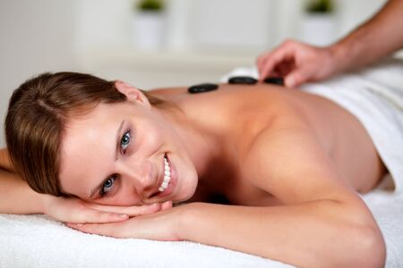 Close up portrait of a relaxed woman receiving a hot stone massage at spa, looking at you photo
