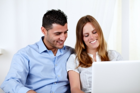 Portrait of a friendly couple using a laptop at home indoor photo