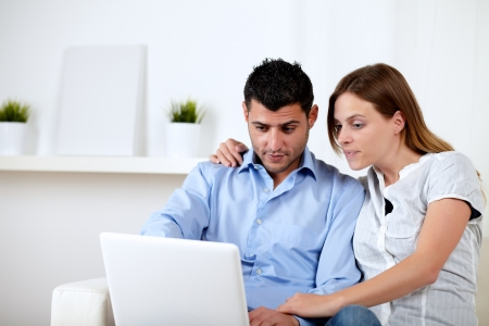 Portrait of a friendly interested couple browsing on laptop at home indoor photo