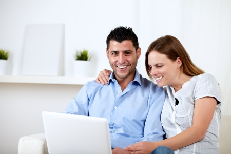 Portrait of a friendly couple having fun on laptop at home indoor photo