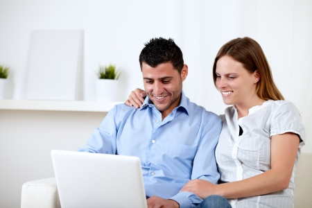 Portrait of a attractive couple smiling and looking to computer screen at home indoor photo