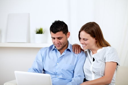 Portrait of a young woman with her boyfriend looking to laptop screen at home indoor photo