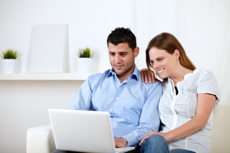 Portrait of a young woman with her boyfriend chatting on laptop at home indoor photo