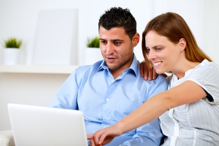 Portrait of a charming young couple sitting on sofa using laptop at home indoor photo