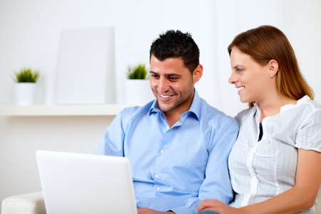 Portrait of a happy young couple sitting on sofa and working on laptop at home photo