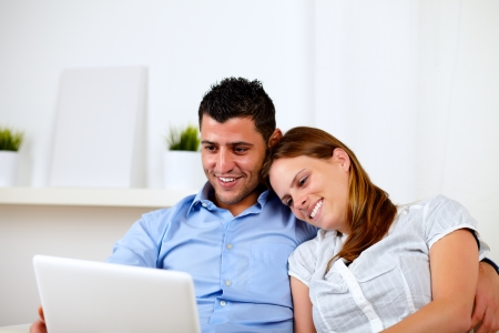 Portrait of a happy young couple sitting on sofa with a laptop at home photo