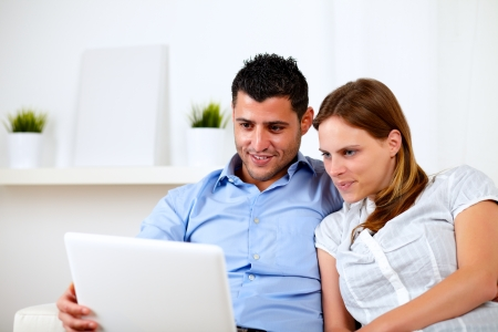 Portrait of a beautiful young couple using laptop together at home indoor photo