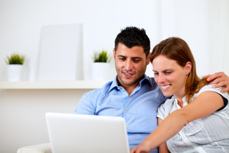 Portrait of a friendly young couple using laptop together at home indoor photo