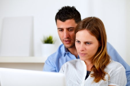 Portrait of a attractive young couple using laptop together at home indoor photo