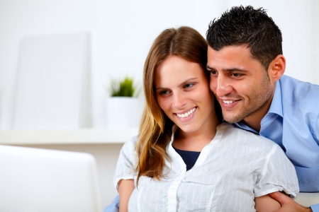 Portrait of a romantic young couple sitting on sofa at home looking to laptop screen photo