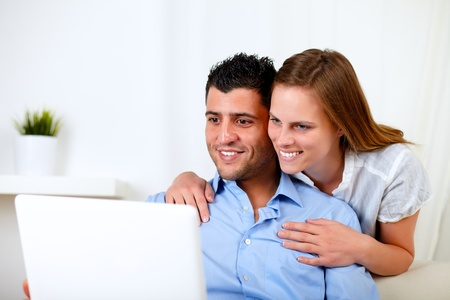 Portrait of a smiling young couple using laptop at home indoor photo