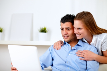 Portrait of a beautiful couple using laptop together at living room at home indoor photo