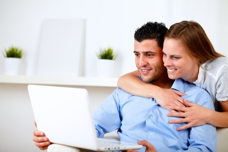 Portrait of a charming couple using laptop together at living room at home indoor