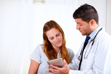 conversing: Portrait of a attractive hispanic doctor conversing with young woman at hospital Stock Photo
