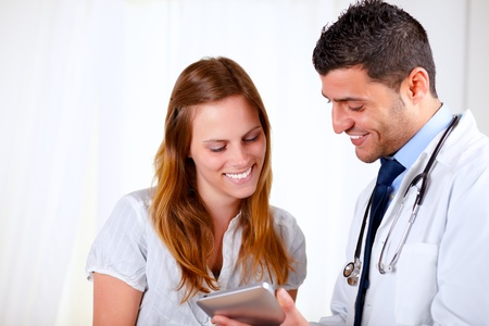 Portrait of a latin doctor and a patient woman looking something on tablet PC at hospital photo